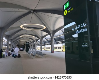 MECCA, SAUDI ARABIA - MAY 27, 2019 :  a group of people in white ihram clothes disembark from train coaches at HSR Mecca station in Mecca, Saudi Arabia.