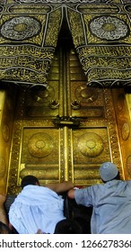 Mecca, Suudi Arabia  / Suudi Arabia - 11.04.2010: Two muslim try to touch the door of Kaba.