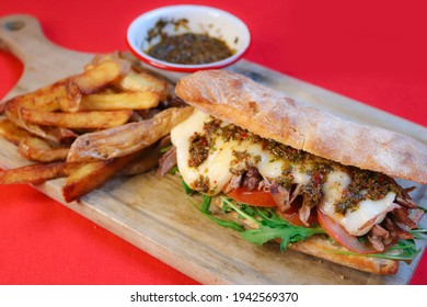MECHADA MEAT SANDWICH, TOMATO, RUCULA, HOMEMADE BREAD WITH SAUCE ON WOODEN BOARD AND FRENCH FRIES MILANESA
