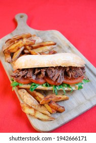 MECHADA MEAT SANDWICH, TOMATO, RUCULA, HOMEMADE BREAD WITH SAUCE ON WOODEN BOARD AND FRENCH FRIES CHIMICHURRI SAUCE, CARAMELIZED ONION, CREOLE SAUCE AND MUSTARD WITH HONEY