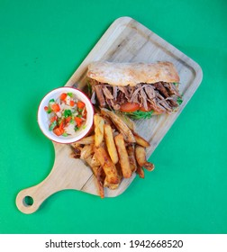 MECHADA MEAT SANDWICH, TOMATO, RUCULA, HOMEMADE BREAD WITH SAUCE ON WOODEN BOARD AND FRENCH FRIES CHIMICHURRI SAUCE, CARAMELIZED ONION, CREOLE SAUCE AND MUSTARD WITH HONEY MILANESA, CHORIPAN, ENTRAÑA