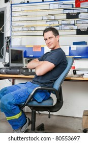 Mechanic with arms crossed sitting on a chair and smiling
