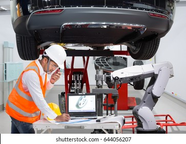 Mechanic with assistance robotic inspection wheel balancing of modern car in automotive industry 4.0 concept