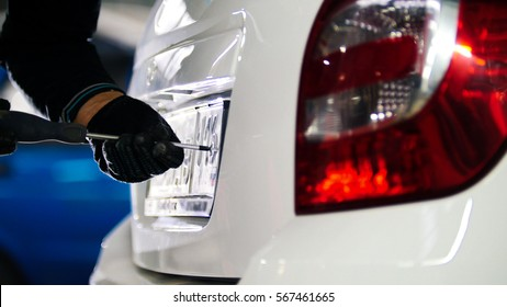 Mechanic in automobile service doing manual operations with car license plate number, telephoto