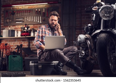 Mechanic or biker working in a workshop on a vintage motorcycle sitting talking on a mobile as he researches information on his laptop