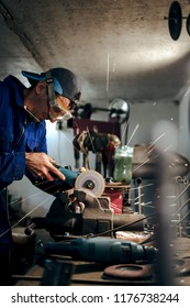 mechanic in blue uniform, cuts the steel part with an angle grinder in the workshop. the concept of protection technology in the workplace, eye protection. sparks fly in the eye, vertical photo