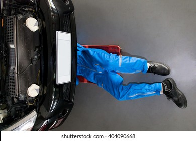 Mechanic in blue uniform lying down and working under car at the repair garage