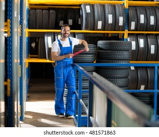 mechanic in blue uniform standing at stock tyre and holding a clipboard
