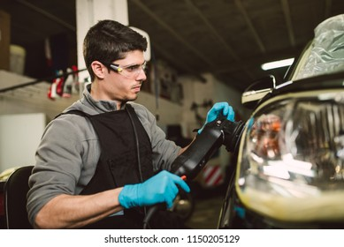 Mechanic with a car polisher in the workshop