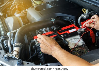 Mechanic car service using Multimeter to check the voltage level in a car battery