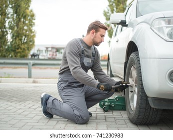The mechanic changes the wheel of the machine outdoors.
