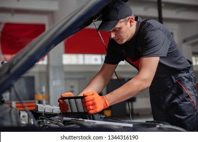Mechanic is changing an air filter. Car hood is open.