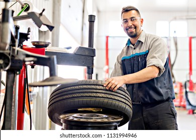 Mechanic changing car tire at work
