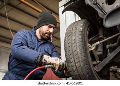Mechanic changing car wheel at service.