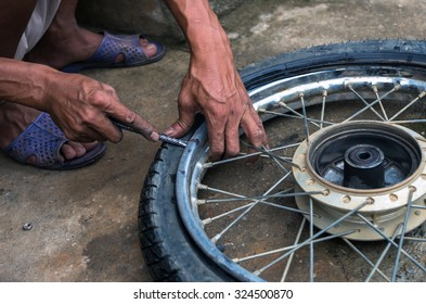 mechanic changing motorcycle tire by traditional method