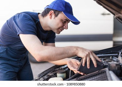 Mechanic changing oil of a car engine, servicing and upkeep concept