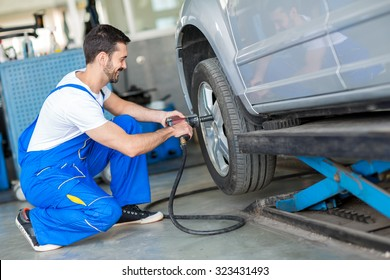 Mechanic changing tyre on car with air wrench in workshop