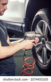 Mechanic changing wheel on car with pneumatic tool