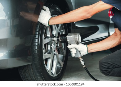 Mechanic changing wheel on car with impact wrench. mechanic man with electric screwdriver changing tire outside. Car service. Hands replace tires on wheels.