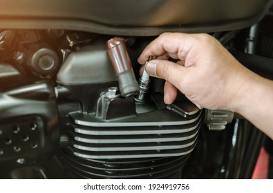Mechanic Check motorcycle Spark Plug and Maintenance, inspection Prior to Installation in engine ignition at motorcycle garage.repair and maintenance motorcycle concept.