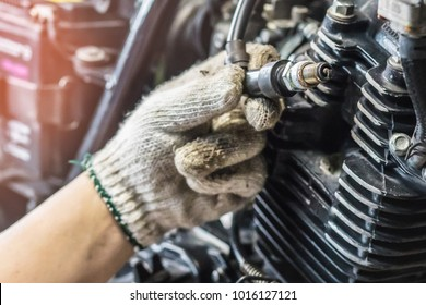 Mechanic Check Spark Plug Inspection and Maintenance, Inspection Prior to Installation in engine ignition and electrical systems at motorcycle garage.repair and maintenance motorcycle concept.
