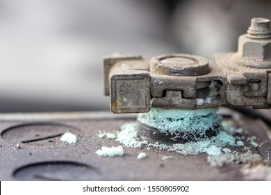 Mechanic checking car Battery terminalin a garage.Old battery corrosion deteriorate leaking with blue acid powder.Battery terminals corrode dirty damaged problem.