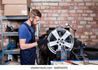 Mechanic checking car wheel rim.