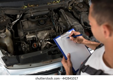Mechanic checking list of car parts on clipboard