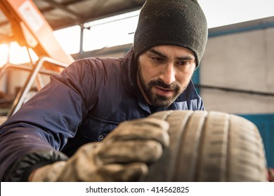 Mechanic, checking a measurement gauge to check the depth of a tread on a car tire for wear, to make sure it is still within regulations and safe to use