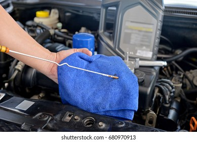 Mechanic checking the motor oil level in the car engine