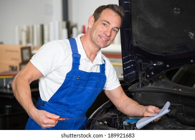 Mechanic checking oil level at a car in garage