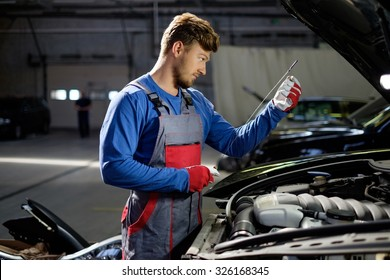 Mechanic checking oil level in a car workshop