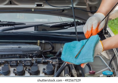 Mechanic checking the oil level of a car engine, normal levels