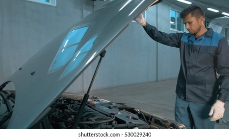 Mechanic checking oil level in a car workshop. Man in truck service  engine.