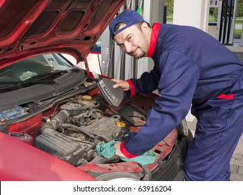 Mechanic Checking Oil Level at Gas Station