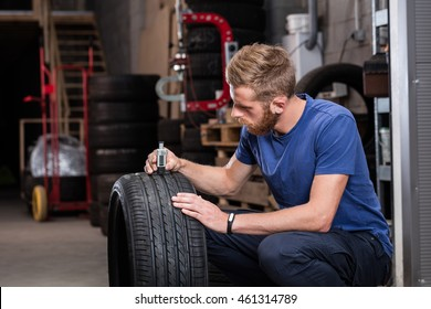 Mechanic checking tread depth on a car tire for wear, to make sure it is still within regulations and safe to use.