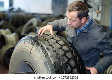 mechanic checking tread on lorry wheel