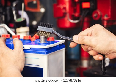 mechanic cleaning a battery connections ,brush and insert the brush into the car's battery terminals,especially if terminals are corroded, will help ensure  the battery lasts longer and performs well