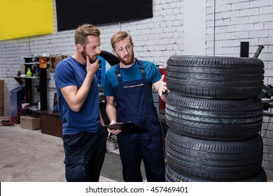 Mechanic and client checking tires  in store.