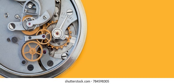 Mechanic clockwork mechanism, spring bronze cogs wheels macro view. Shallow depth of field, selective focus. Yellow colorful background. Copy space