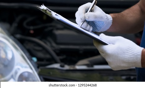 Mechanic diagnoses car, writing costings, annual vehicle inspection, close up