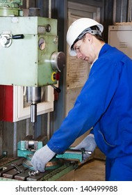 the mechanic dressed in overalls, works at the boring machine