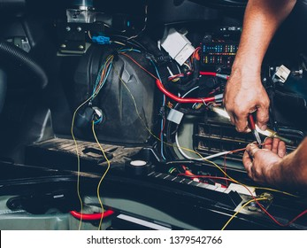 Mechanic electrician checking repairing upgrading wiring. Auto service workshop. Regular preventive car maintenance.