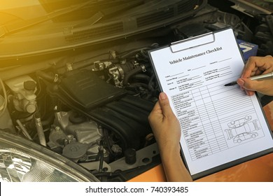 Mechanic engineer hand holding checklist paper and taking a note on clipboard with car engine background.