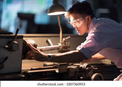 Mechanic Engineer Turner Miller verifies the accuracy of manufacturing steel parts with a scale the size of the measurement device. In the dark room with lamp background.