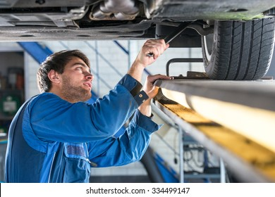 Mechanic, examining the suspension of a vehicle with a steel rod for any undesired clearances as part of a periodical vehicle safety inspection or mot test