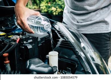 mechanic fill fresh water into windscreen or in water tank wiper on car engine room.
