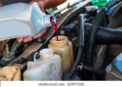 Mechanic filling red hydraulic oil in service shop