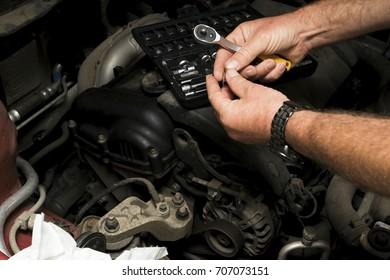 The mechanic fixes the vehicle's engine