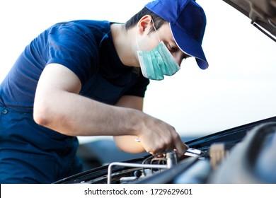 Mechanic fixing a car engine wearing a mask, coronavirus concept